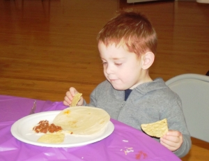 Little redhead boy eating
